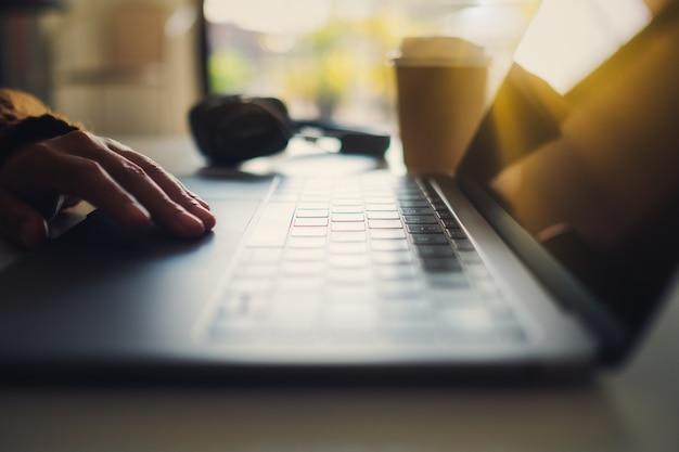 テーブルの上のラップトップのタッチパッドで作業し、触れている手のクローズアップ画像