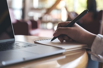 Closeup image of hand writing down on a blank notebook with laptop on wooden table
