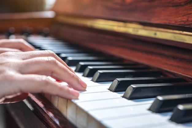 Крупным планом изображение рук, играющих на старинном деревянном рояле