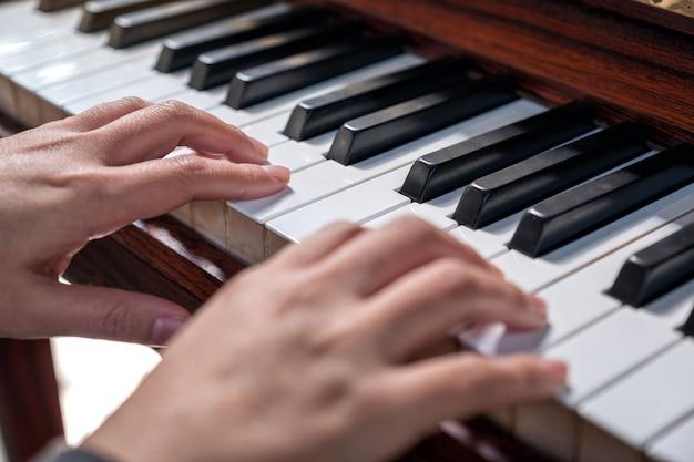 ヴィンテージ木製グランドピアノを弾く手のクローズアップ画像
