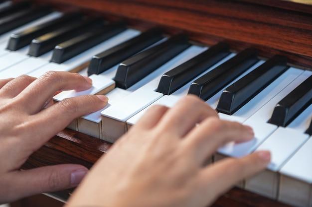 빈티지 나무 그랜드 피아노를 연주하는 손의 근접 촬영 이미지