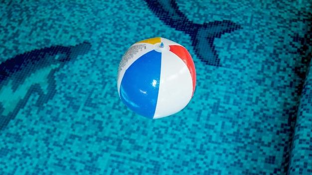 スイミングプールのインフレータブルビーチボールのクローズアップ画像。休日の夏のビーチでの休暇を説明するのに最適な画像