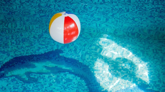 Изображение крупного плана надувного пляжного мяча в бассейне. идеальное изображение для иллюстрации летнего пляжного отдыха во время отпуска