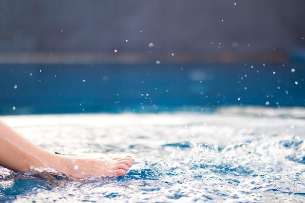 プールで水を蹴ってはねかける足と素足のクローズアップ画像