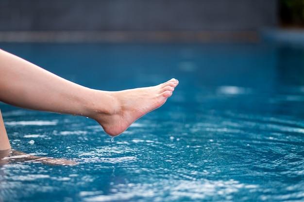 足と裸足で蹴ってプールに水を浸すクローズアップ画像