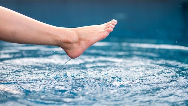 プールで足と裸足の蹴りと水しぶきのクローズアップ画像