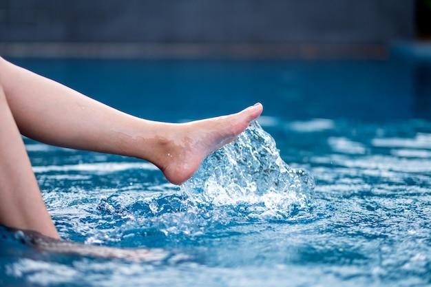 プールで足と左足を蹴って水をはねかけるクローズアップ画像