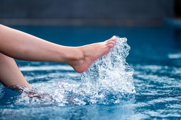 プールで足と右足を蹴って水をはねかけるクローズアップ画像