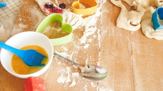 木製の机の上の料理やパン屋のための多くの食材とキッチン ツールのクローズ アップ画像