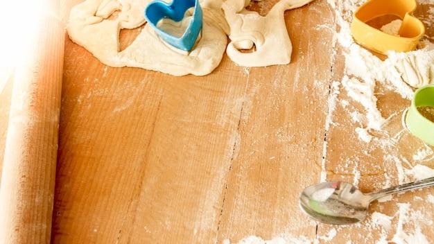木製の机の上の料理やパン屋のためのたくさんの食材やキッチンツールのクローズアップ画像