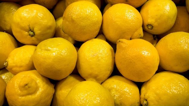 Изображение крупного плана множества органических лимонов, лежащих на прилавке магазина. текстура крупного плана или картина свежих спелых фруктов. красивый фон еды
