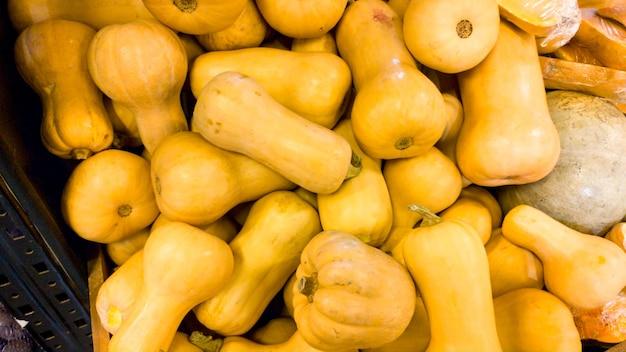 Изображение крупного плана серий спелых тыкв, лежащих на прилавке в продуктовом магазине. текстура крупного плана или картина свежих спелых овощей. красивый фон еды