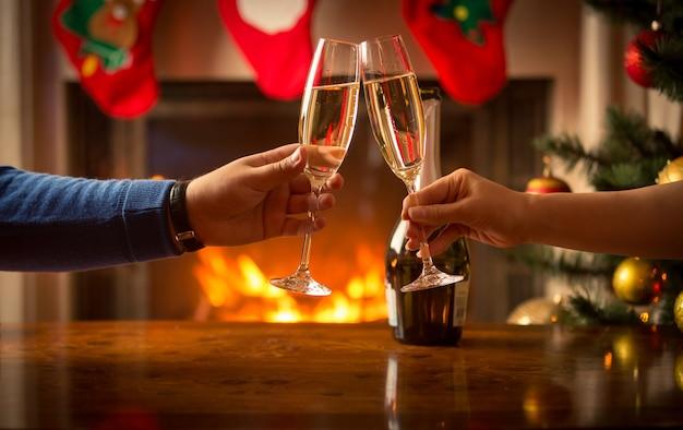 크리스마스로 장식된 거실에서 샴페인 잔으로 부딪치는 남성과 여성의 손을 클로즈업한 이미지