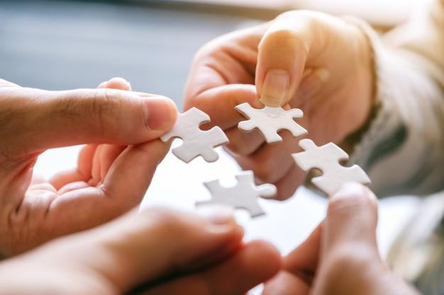 Крупным планом изображение многих людей, держащих и складывающих кусок белой головоломки вместе