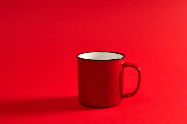 Изображение крупного плана одной красной чашки чая или горячего напитка на красном фоне с мягкой тенью и копией пространства для продвижения. красная кружка.