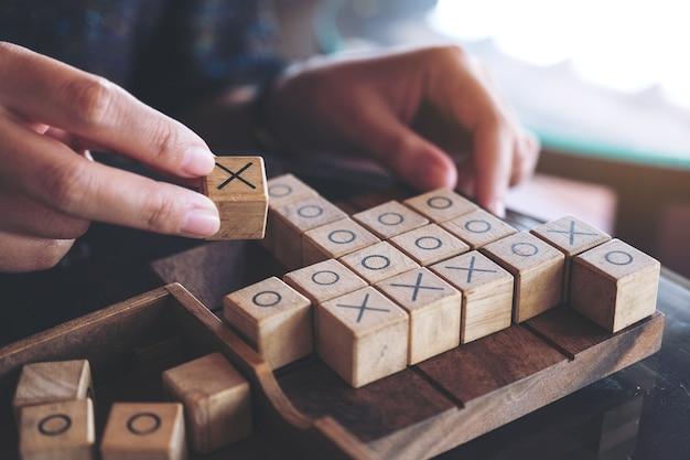 Макрофотография изображение людей, играющих деревянных tic tac toe игра или игра ox