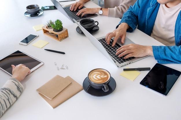 사무실 테이블에 노트북 컴퓨터와 태블릿 pc를 사용하고 작업하는 사람들의 근접 촬영 이미지