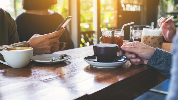 Крупным планом изображение людей, использующих мобильный телефон и пить кофе вместе в кафе