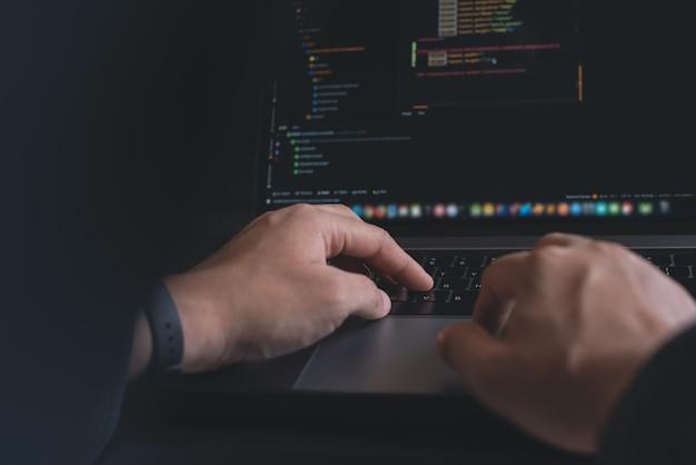 ラップトップコンピューターでjavascriptをコーディングするプログラマーのクローズアップ画像