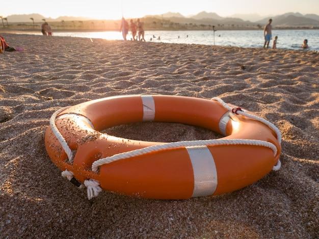 夕日の光で砂浜の海に赤いプラスチックの救命リングのクローズ アップ画像