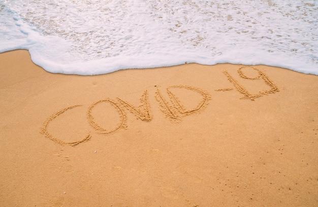 Крупным планом изображение морских волн, смывающих слово «covid-19» с песка на пляже