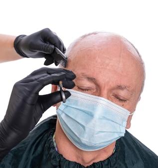 理髪店の保護フェイスマスクで年配の男性のクローズアップ画像。はさみで髪を切る理髪店