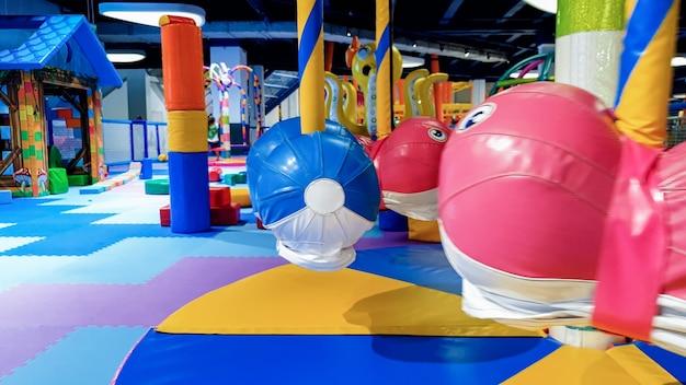 Изображение крупным планом маленькой детской карусели, покрытой мягкими ковриками для безопасности детей на игровой площадке в торговом центре