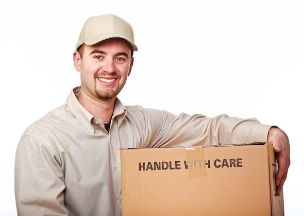 Крупным планом изображение улыбающегося молодого кавказского доставщика с посылкой