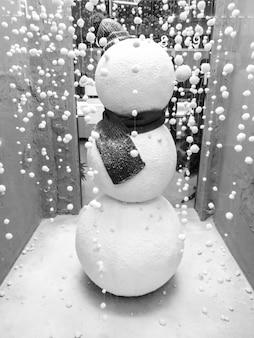 Крупным планом изображение снеговика в черном шарфе на ветру рождественского магазина