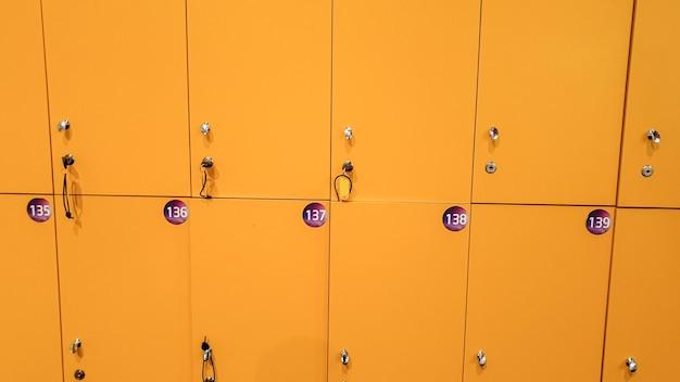 Изображение крупным планом прямых длинных рядов желтых шкафчиков в школе или колледже