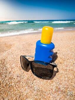 砂浜のサングラスと日焼け止めローションのクローズアップ画像。夏休みのイラストにぴったりの画像です。