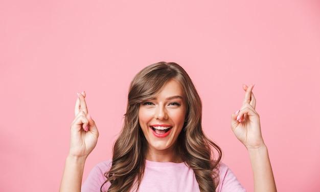 Крупным планом изображение суеверной европейской женщины в простой одежде, скрестив пальцы на обеих руках и мечтающей об удаче, изолированное на розовом фоне