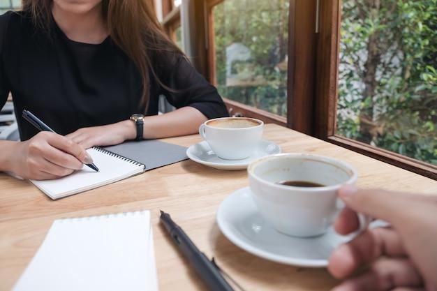 Изображение крупного плана кофе 2 бизнесменов выпивая пока говорящ и встречающ в офисе