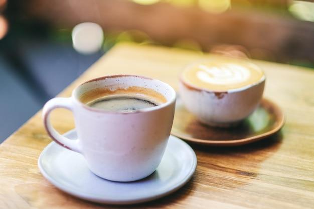나무 테이블에 뜨거운 라떼 커피와 아메리카노 커피 두 잔의 클로즈업 이미지