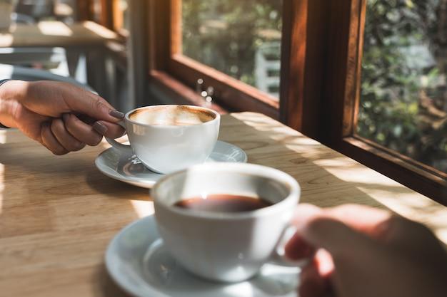 Изображение крупного плана 2 людей держа и выпивая кофе утром