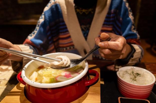 野菜と豚肉と鍋を食べる女性のクローズアップ画像