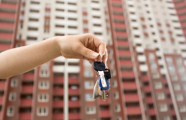 새 건물 앞의 새 아파트에서 키를 들고 여자의 근접 촬영 이미지 프리미엄 사진