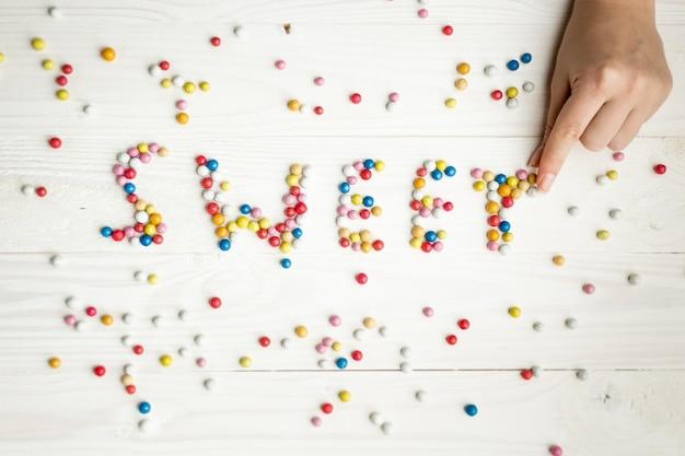Крупным планом изображение женщины, делая слово сладкое из красочных конфет
