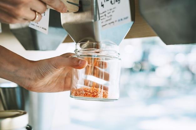 女性のクローズアップ画像は、プラスチックの無料食料品店のディスペンサーからガラスの瓶に赤レンズ豆を注ぐ