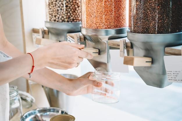 女性のクローズアップ画像は、ゼロウェイストショップのディスペンサーからガラスの瓶に赤レンズ豆を注ぐ
