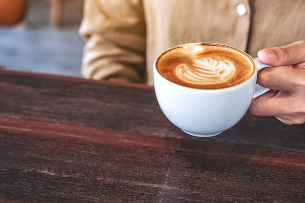 カフェの木製テーブルにホットコーヒーのカップを保持している女性の手のクローズアップ画像