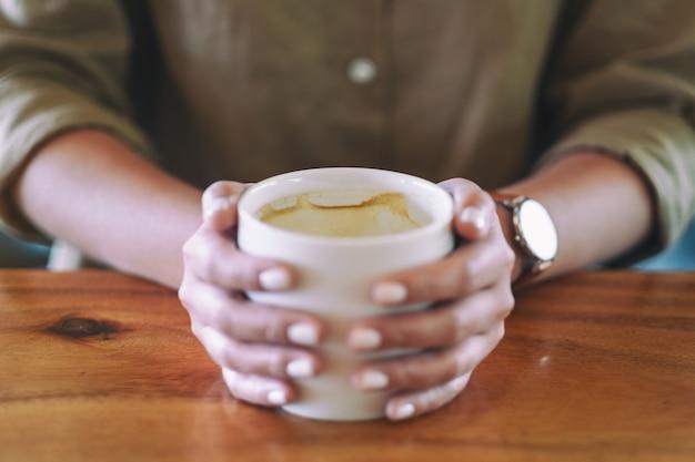 木製のテーブルにホットコーヒーのカップを保持している女性の手のクローズアップ画像