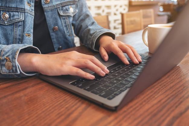 Крупным планом изображение женских рук, использующих и печатающих на клавиатуре портативного компьютера с чашкой кофе на столе