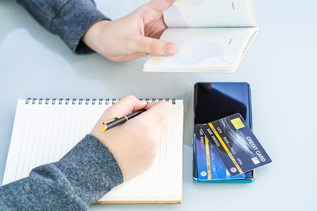 クレジットカードとスマートフォンのデスクでノートに書く女性のクローズアップ画像