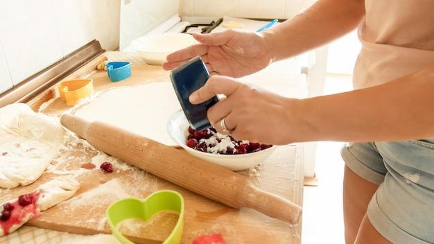 パイのソースを作りながらfgreshベリーと大きなボウルに砂糖を注ぐ若い主婦のクローズアップ画像