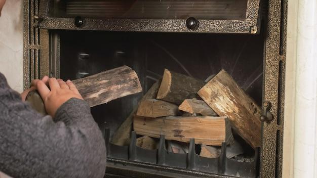 Крупным планом изображение молодого человека, бросающего дрова в камин