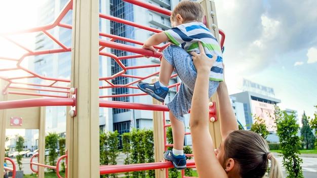 スポーツの子供たちの遊び場で彼女の幼い息子が高い金属の階段に登るのを助ける若い母親のクローズアップ画像