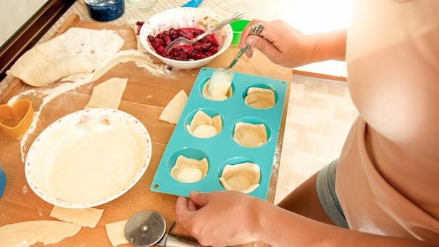 Изображение крупного плана молодой женщины делая кексы. девушка кладет крем внутрь теста в силиконовые формы для выпечки