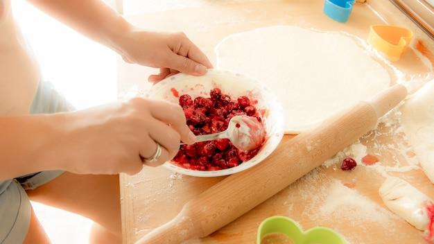 ベリーと砂糖を混ぜる若い女性のクローズアップ画像。甘いパイのベリーソースを作る主婦