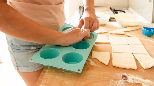 젊은 여자의 근접 촬영 이미지 반죽 조각을 집어 오븐에서 베이킹을 위해 실리콘 형태로 넣어